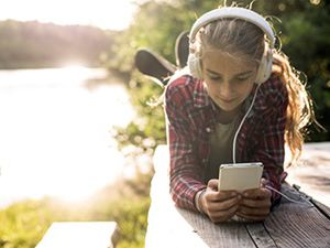 Young woman at lakefront dock stays connected on her mobile and headphones