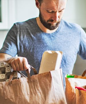 Man with bags of groceries in the kitchen