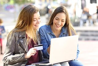 Two young ladies shopping online with their debit cards